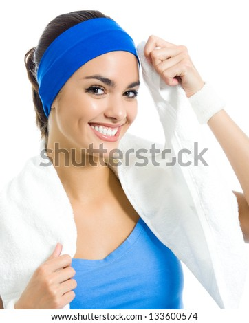 Cheerful young woman in fitness wear with towel, isolated over white background