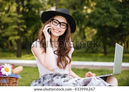 Cheerful young woman in hat and glasses talking on cell phone and using laptop outdoors