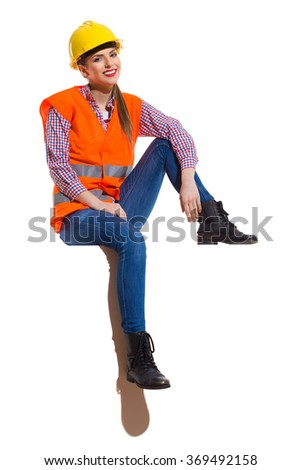 Cheerful young woman in orange reflective vest, lumberjack shirt, jeans, black boots, sitting on a top. Full length studio shot isolated on white. - stock photo