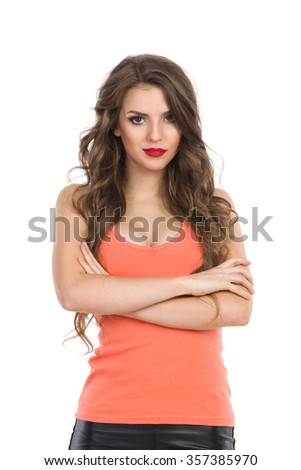 Cheerful young woman in orange shirt with sexy neckline standing with arms crossed and looking at camera. Waist up studio shot isolated on white. - stock photo