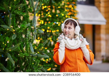 Cheerful young woman in Paris on a winter day, enjoying Christmas season - stock photo