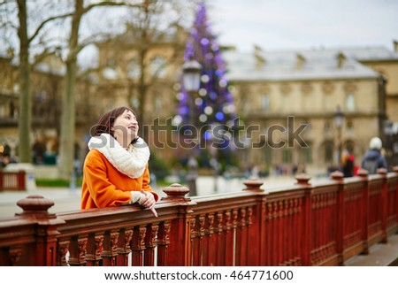 Cheerful young woman in Paris on winter day, decorated Christmas tree in the background