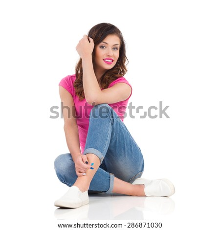 Cheerful young woman in pink shirt and jeans sitting on a floor. Full length studio shot isolated on white. - stock photo