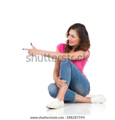 Cheerful young woman in pink shirt and jeans sitting on a floor, pointing and looking away. Full length studio shot isolated on white. - stock photo