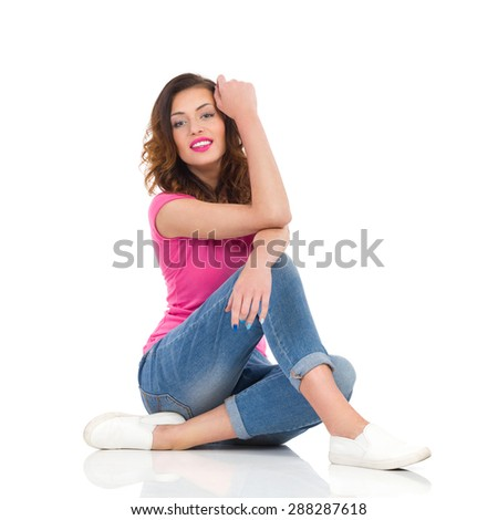 Cheerful young woman in pink shirt and jeans sitting on the floor. Full length studio shot isolated on white. - stock photo