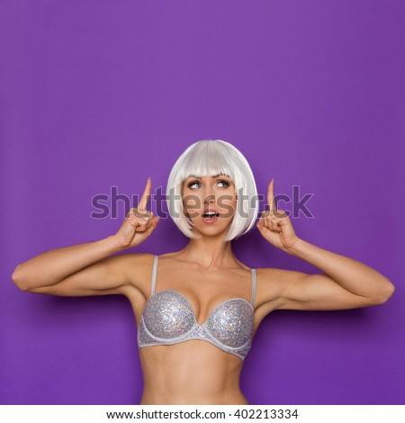 Cheerful young woman in platinum wig and silver bra pointing and looking up at copy space. Waist up studio shot on purple background. - stock photo