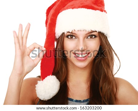 cheerful young woman in santa hat showing ok sign.isolated on white background - stock photo