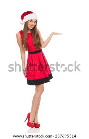 Cheerful young woman in santa's hat and red dress standing and presenting product. Full length studio shot isolated on white. - stock photo