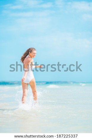 Cheerful young woman in swimsuit walking on sea shore