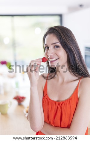cheerful young woman in the kitchen with a strawberry in hand - stock photo