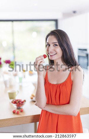 cheerful young woman in the kitchen with a strawberry in hand