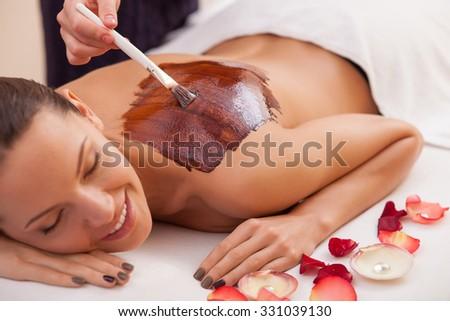 Cheerful young woman is getting chocolate massage at spa. She is lying and relaxing. Her eyes are closed with pretty smile. The masseuse is holding brush and applying substance on female back