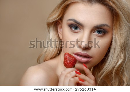 Cheerful young woman is holding strawberry near her face. She is looking at the camera with temptation. Isolated on brown background and there is copy space in left side - stock photo
