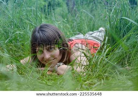 Cheerful young woman is lying in the green grass. She is resting in the meadow. - stock photo