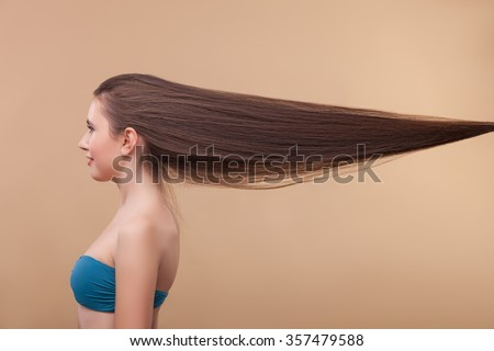 Cheerful young woman is showing her long straight hair. She is standing and smiling. Isolated on brown background - stock photo