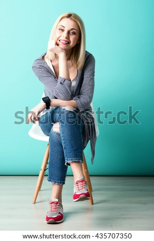 Cheerful young woman is sitting with anticipation - stock photo