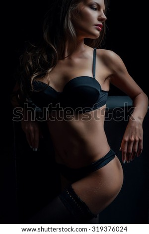 Cheerful young woman is standing and leaning on dark surface. She has attractive underwear. The lady is looking aside with desire - stock photo