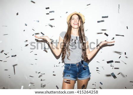 Cheerful young woman is stretching out her hands while confetti falling on her. - stock photo