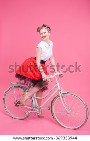 Cheerful young woman is traveling by cycle - stock photo