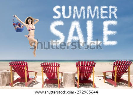 Cheerful young woman leaps over beach chairs with summer sale cloud - stock photo