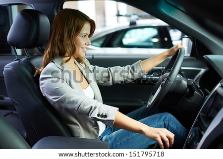 Cheerful young woman learning to drive on her own - stock photo