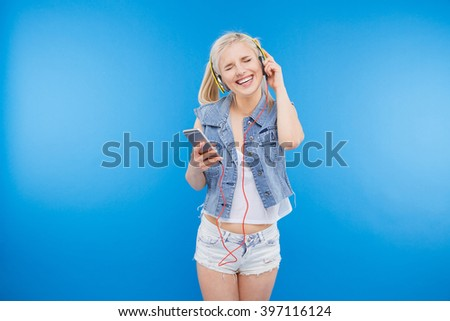Cheerful young woman listening music in headset on smartphone over blue background