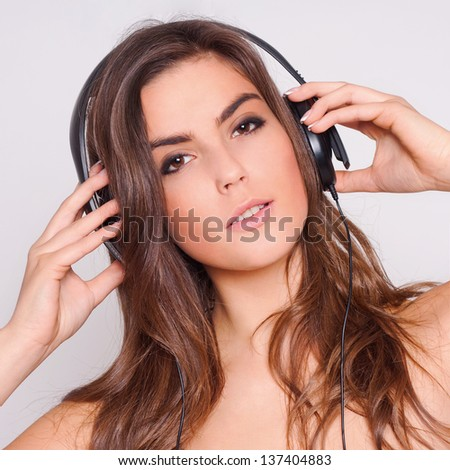 Cheerful young woman listening music with headphones.  on white background.