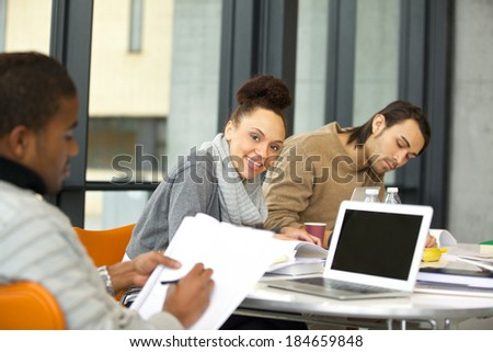 Cheerful young woman looking at camera while studying. University students studying with books and laptop in library. - stock photo
