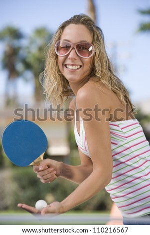 Cheerful young woman playing table tennis