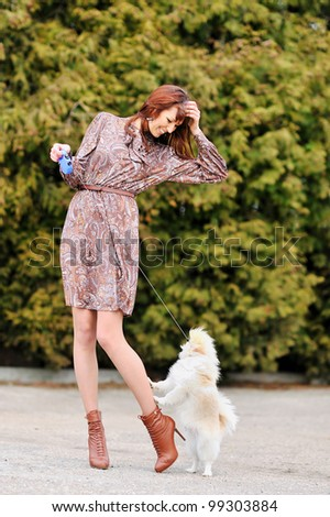 Cheerful young woman playing with her puppy - stock photo