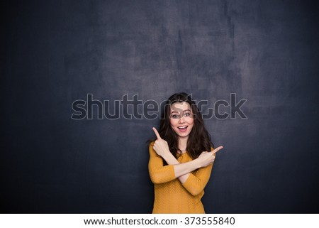 Cheerful young woman pointing fingers away over black background - stock photo