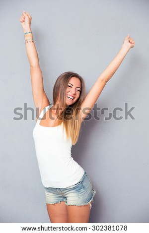 Cheerful young woman posing over gray background - stock photo