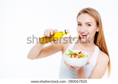Cheerful young woman poured oil into salad isolated on a white background - stock photo