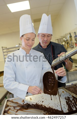 cheerful young woman professional pastry uses chocolate for tasty recipe