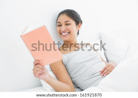 Cheerful young woman reading a book in bed at home - stock photo