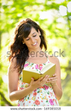 Cheerful young woman reading book while walking in park on spring or summer. Beautiful girl enjoying interesting novel. - stock photo