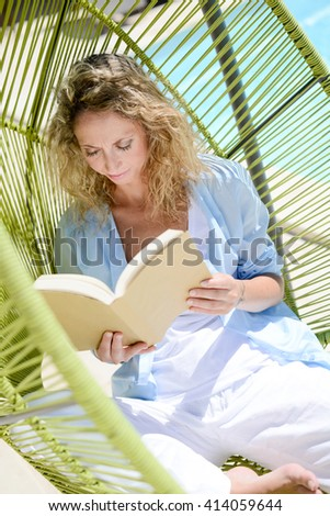 cheerful young woman reading in a hammock by the pool on sunny summer day