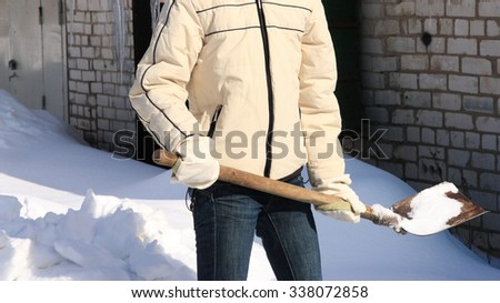 Cheerful young woman removing snow with a shovel; manual snow removal - stock photo