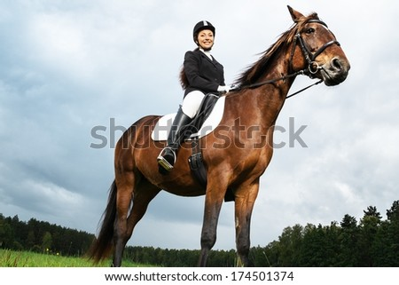 Cheerful young woman ridding horse in a field  - stock photo