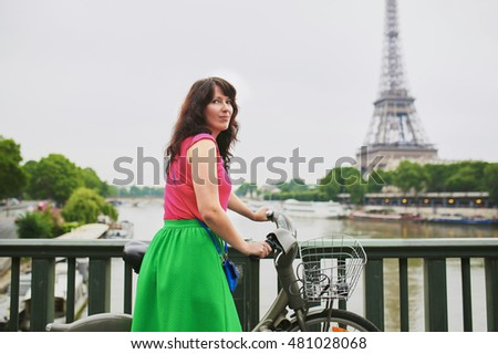 Cheerful young woman riding a bicycle on a street of Paris, near the Eiffel tower