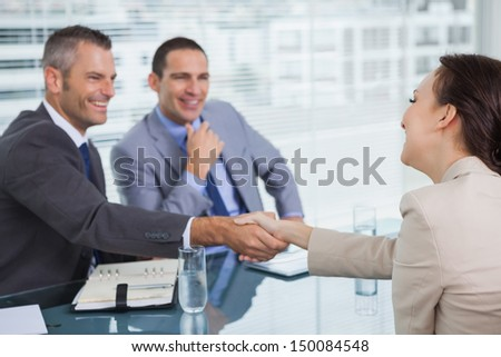 Cheerful young woman shaking hands with her future employer in bright office - stock photo