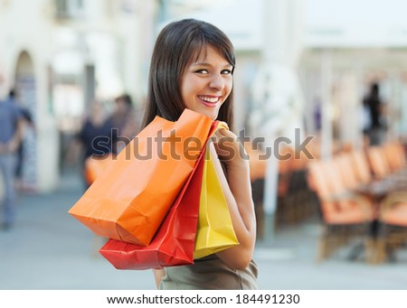 Cheerful young woman shopping in the city.