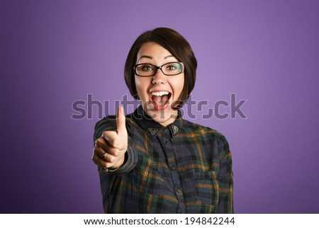 Cheerful young woman showing thumb up sign on purple background - stock photo