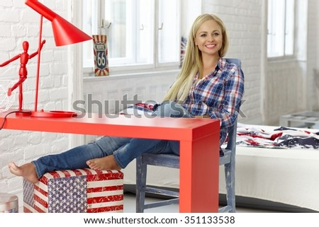 Cheerful young woman sitting at desk at home, smiling happy. - stock photo