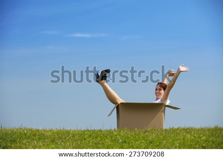 Cheerful young woman sitting in cardboard box at park with arms outstretched - stock photo