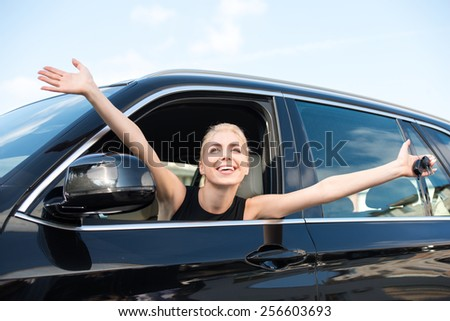 Cheerful young woman sitting inside new car with keys to it. Concept for car rental
