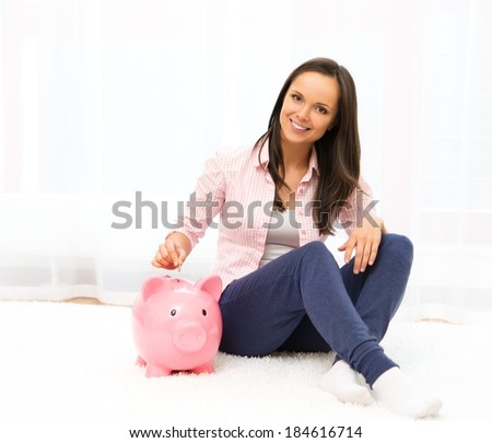 Cheerful young woman sitting on a carpet with piggybank - stock photo