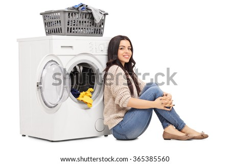 Cheerful young woman sitting on the floor next to a washing machine isolated on white background