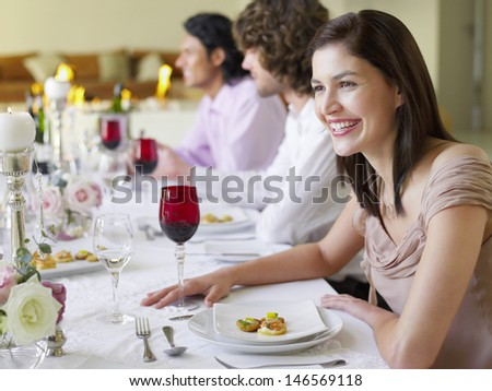 Cheerful young woman sitting with friends at dinner party - stock photo