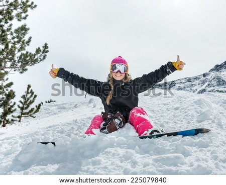 Cheerful young woman snowboarder sitting in the snow wearing a mask shows a sign on the background of beautiful mountains - stock photo